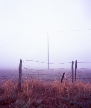 Pylon in the fog, with fence