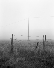Fence and pylon in the fog